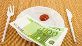 De honger voor geld, 100 euroservetten, ketchup, plastic vork en mes stock afbeelding