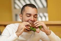 De hongerige jonge mens in resaurant eet sandwich stock afbeeldingen