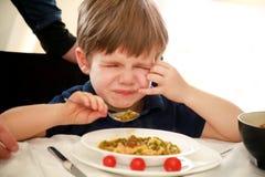 De hongerige kindzitting als voorzitter bij lijst in keuken en veracht, keurt hete maaltijd af, omdat hij van geen lunch houdt royalty-vrije stock afbeeldingen