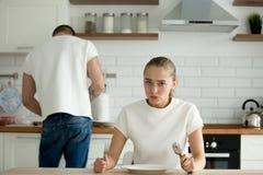 De hongerige vrouw kijkt ontevreden wachten voor echtgenoot het koken stock afbeeldingen