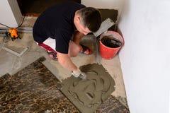 De hoofdechtgenoot drukt een spatel glutineuze oplossing aan de cementoppervlakte stock fotografie