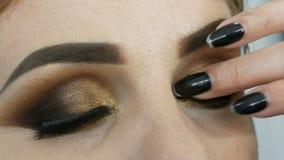 De hoofdgrimeur past professionele samenstellings gouden rokerige ogen in schoonheidssalon op een vet vrouwenmodel met toe blauwe stock video