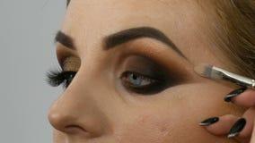 De hoofdgrimeur past professionele samenstellings gouden rokerige ogen in schoonheidssalon op een vet vrouwenmodel met toe blauwe stock videobeelden