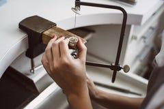 De hoofdhand van ` s Sluit omhoog van de handen die van een vrouwelijke juwelier aan een ring bij haar werkbank werken royalty-vrije stock afbeelding