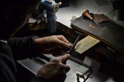 De hoofdjuwelier houdt het werkende hulpmiddel in zijn handen en maakt juwelen bij zijn werkplaats in de juwelenworkshop stock fotografie