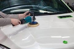 De hoofdman van het detailleren in het werkkleren en vuile handen poetst de carrosserie van de bonnet van de auto in wit met a op stock afbeeldingen