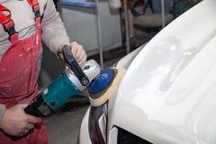 De hoofdman van het detailleren in het werkkleren en vuile handen poetst de carrosserie van de bonnet van de auto in wit met a op stock foto's