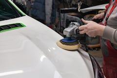 De hoofdman van het detailleren in het werkkleren en vuile handen poetst de carrosserie van de bonnet van de auto in wit met a op stock fotografie