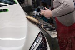 De hoofdman van het detailleren in het werkkleren en vuile handen poetst de carrosserie van de bonnet van de auto in wit met a op stock foto