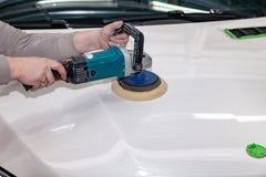 De hoofdman van het detailleren in het werkkleren en vuile handen poetst de carrosserie van de bonnet van de auto in wit met a op royalty-vrije stock afbeelding