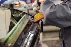 De hoofdman van het detailleren in het werkkleren en vuile handen poetst de carrosserie van de bonnet van de auto in zwarte met a royalty-vrije stock fotografie