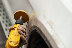 De hoofdman van het detailleren in het werkkleren en de vuile handen schuren de carrosserie van het stootkussen van de auto in wi royalty-vrije stock afbeeldingen