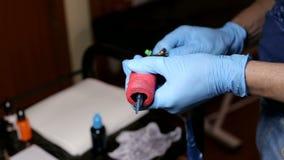 De hoofdtatoegeringskunstenaar bereidt hulpmiddelen om te tatoeëren voor stock videobeelden