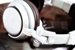 De hoofdtelefoons die van DJ over oud vinyl liggen Stock Foto's
