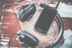 De hoofdtelefoons en de telefoon uitstekende foto's, luisteren aan muziek stock afbeeldingen