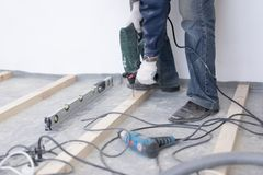 De hoofdtimmerman zet de vloer van het pijnboomhout op - milieuvriendelijke bevloering het schroeven vertraging aan beton stock foto