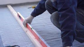 De hoofdtimmerman zet de vloer van het pijnboomhout op - milieuvriendelijke bevloering het schroeven vertraging aan beton stock videobeelden