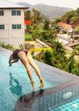 De hoofdvoorzijde van de meisjessprong in het openlucht zwembad Stock Foto's