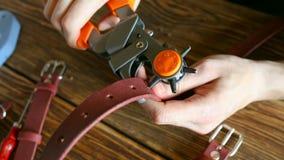 De hoofdwerken met gatenstempel en stuk van leer Close-up Op bruine houten die lijst met hulpmiddelen en toebehoren wordt verspre stock footage
