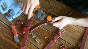 De hoofdwerken met gatenstempel en stuk van leer Op bruine houten die lijst met hulpmiddelen en toebehoren wordt verspreid stock video