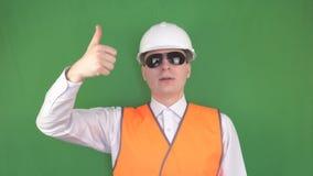 De hoofdwerkgever in zwarte glazen op het werk geeft het bevel aan de kraanmachinist om de groene lading op te heffen, stock video