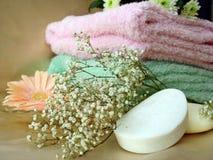 De hoofdzaak van het kuuroord (zeep en handdoeken met roze bloemen) Royalty-vrije Stock Foto's
