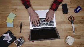 De hoogste die mening onderaan schot van zakenman wordt gesloten overhandigt ons ring een laptop, toetsenbord en cork lijst stock footage