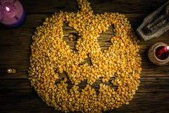 De hoogste die pitten van het meningsgraan in een Halloween-masker worden geschikt op oude houten lijst royalty-vrije stock foto's