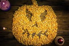 De hoogste die pitten van het meningsgraan in een Halloween-masker worden geschikt op oude houten lijst royalty-vrije stock foto