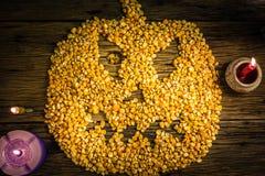 De hoogste die pitten van het meningsgraan in een Halloween-masker worden geschikt op oude houten lijst royalty-vrije stock afbeelding