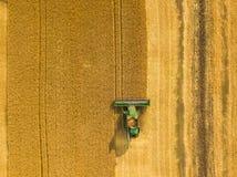 De hoogste mening maaidorser verzamelt de tarwe bij zonsondergang Harvesti royalty-vrije stock afbeelding