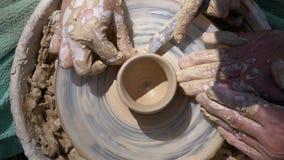 De hoogste mening over Pottenbakkers` s handen werkt met klei aan een pottenbakkers` s wiel stock video