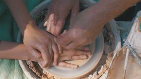 De hoogste mening over Pottenbakkers` s handen werkt met klei aan een pottenbakkers` s wiel stock videobeelden
