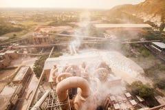 De hoogste mening van cementfabriek, stoffig en stoom blies in de fabriek, het dorp en de berg in het stof in de hete avond, stock foto