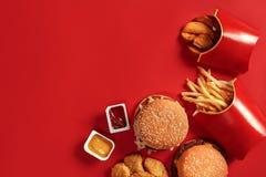 De hoogste mening van de snel voedselschotel Vleeshamburger, chips en goudklompjes op rode achtergrond Meeneemsamenstelling Royalty-vrije Stock Afbeeldingen