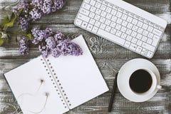 De hoogste mening van een agenda, het toetsenbord, de hoofdtelefoons en een kop van koffie en purple bloeien op een grijze houten Royalty-vrije Stock Afbeeldingen