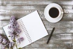 De hoogste mening van een agenda of een notitieboekje, het potlood en de koffie en purple bloeien op een grijze houten lijst Vlak Stock Afbeelding