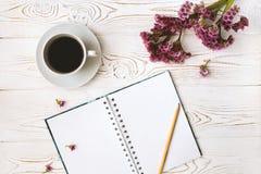 De hoogste mening van een agenda of een notitieboekje, het potlood en de koffie en purple bloeien op een witte houten lijst Vlak  Royalty-vrije Stock Fotografie