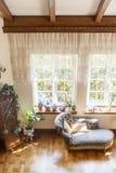 De hoogste mening van een chaise-longue, de vensters en de gordijnen in een klassieke stijl huisvesten binnenland royalty-vrije stock afbeeldingen