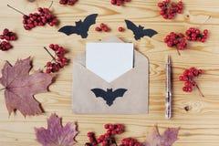 De hoogste mening van een houten Desktop van Halloween met document, pen, envelop, knuppels, bessen en esdoorn gaat weg Met exemp Stock Foto's