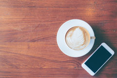 De hoogste mening van een kop van hete koffie en smartphone zetten op oude houten Royalty-vrije Stock Afbeeldingen