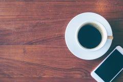 De hoogste mening van een kop van hete koffie en smartphone zetten op oude houten Stock Foto's