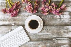 De hoogste mening van een toetsenbord, de hoofdtelefoons en een kop van koffie en purple bloeien op een grijze houten lijst Vlak  Royalty-vrije Stock Fotografie