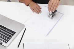 De hoogste mening van een vrouw in bruine blouse gebruikt een zegel stock fotografie