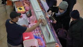 De hoogste mening van de handel drijvende afdeling van de vissenmarkt, vrouw koopt pijlinktvis stock video