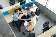De hoogste mening van het jonge partners schudden overhandigt overeenkomst op kantoor Nadruk op handschok stock foto