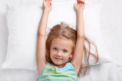 De hoogste mening van mooi kind heeft lang haar, uitrekt zich in bed, ligt op wit hoofdkussen, heeft vroeg goede stemming na rust stock afbeeldingen