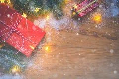 De hoogste mening van stelt, de takken van de pijnboomboom, Kerstmisballen en lichten op houten achtergrond met sneeuwbekleding v stock foto's