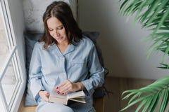 De hoogste mening van tevreden vrouw met dark het lange die haar, in boek wordt geconcentreerd, iets leest die opwekken, geniet v stock foto