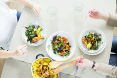 De hoogste mening van twee jonge vrouwen die groene salades eten met chiken en aardappel royalty-vrije stock foto